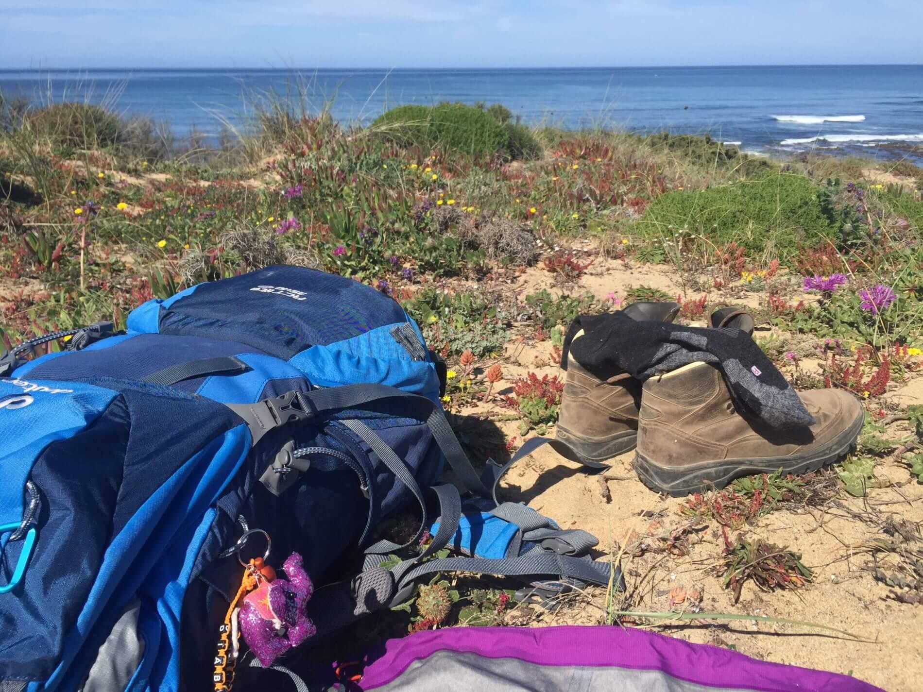 Rota Vicentina_Fishermen's Trail_Pausenensemble mit Rucksack und Wandersteifeln am Atlantik